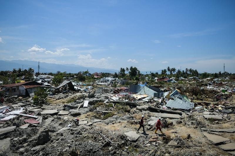 Rescuers walk past debris in Palu, Indonesia's Central Sulawesi, following the September 2018 earthquake and tsunami (AFP Photo/MOHD RASFAN)