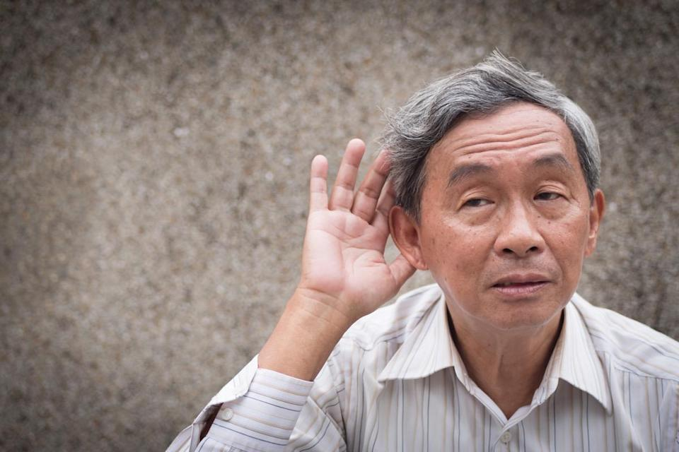 sad senior listening, old man hearing concept of deafness or hard of hearing
