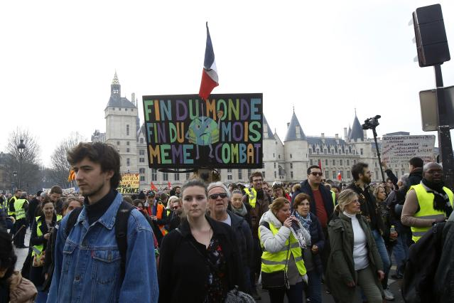 """A protester holds a placard reads in French """"End Of The World, End Of The Month, Same Combat """"during a rally in Paris, Saturday, March 23, 2019. Yellow vest demonstrators gathered in Paris and other French cities for a 19th round of demonstrations as authorities issued bans on protests in certain areas and enhanced security measures in an effort to avoid a repeat of last week's riots in the capital. (AP Photo/Michel Euler)"""