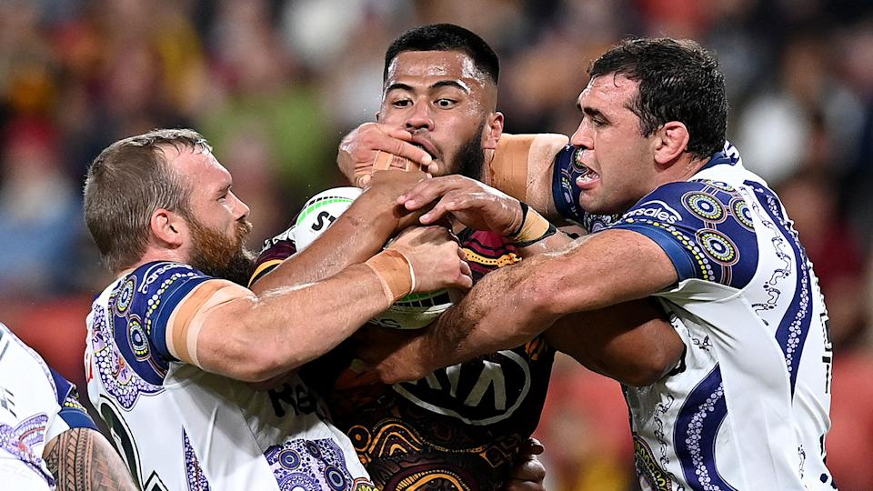 Brisbane's Payne Haas is seen here being tackled by Melbourne Storm players.