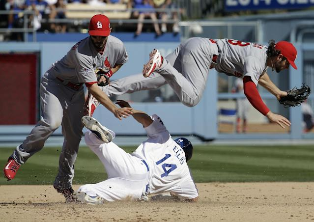 Los Angeles Dodgers' Mark Ellis (14) tries to break up a double play as he gets tangled with St. Louis Cardinals' Pete Kozma (38) and Matt Carpenter (13) during the third inning of Game 5 of the National League baseball championship series Wednesday, Oct. 16, 2013, in Los Angeles. Matt Carpenter was out at first. (AP Photo/David J. Phillip)