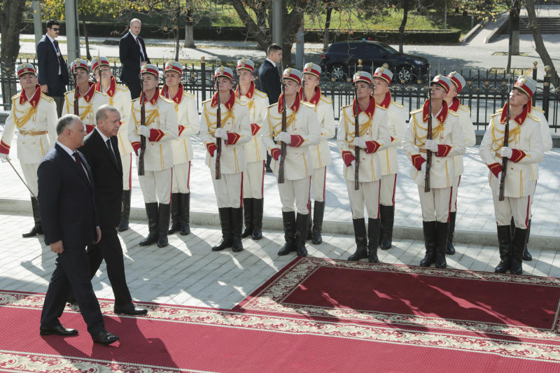 Turkey's President Recep Tayyip Erdogan, SECOND left, and Moldova's President Igor Dodon inspect a military honour guard during a welcome ceremony in Kishinev, Moldova, Wednesday, Oct. 17, 2018. Erdogan is in Moldova for a two-day state visit. (Presidential Press Service via AP, Pool)