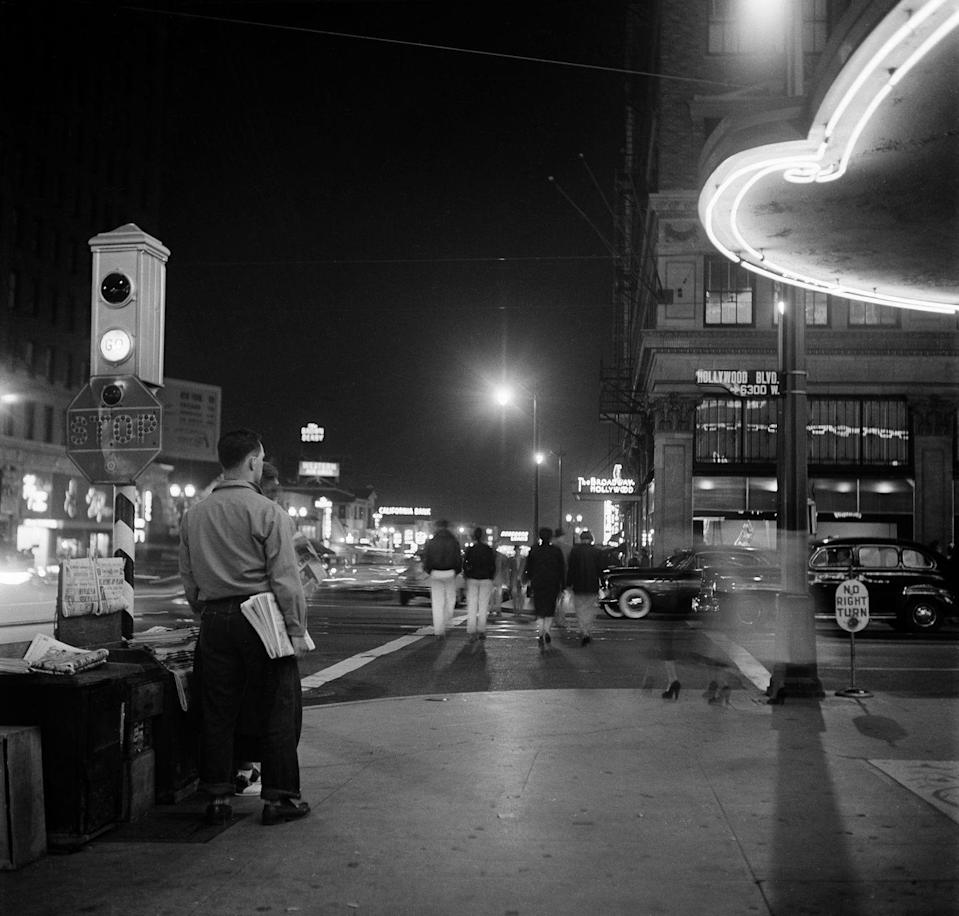 <p>People walk along Hollywood Boulevard at night. </p>
