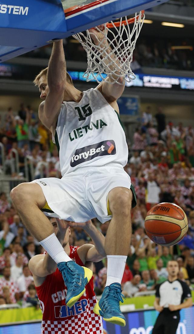 Lithuania's Robertas Javtokas hangs on a rim after dunking a ball during the EuroBasket European Basketball Championship semifinal match against Croatia in Ljubljana, Slovenia, Friday, Sept. 20, 2013. (AP Photo/Petr David Josek)