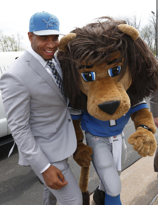 """Detroit Lions first round draft choice, 10th overall, North Carolina tight end Eric Ebron walks with team mascot """"Roary"""" after arriving at the team's headquarters in Allen Park, Mich., Friday, May 9, 2014. (AP Photo/Paul Sancya)"""