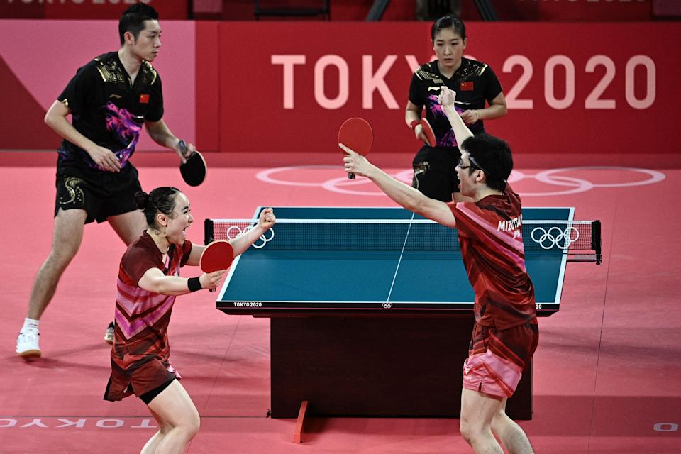 Japan's Jun Mizutani (R) and Mima Ito (2L) celebrate beating China's Xu Xin (L) and Liu Shiwen (TOP R) in their mixed doubles table tennis final match at the Tokyo Metropolitan Gymnasium during the Tokyo 2020 Olympic Games in Tokyo on July 26, 2021. (Photo by Anne-Christine POUJOULAT / AFP) (Photo by ANNE-CHRISTINE POUJOULAT/AFP via Getty Images)