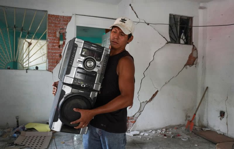 A man carries a stereo at his home damaged by a quake in Huatulco