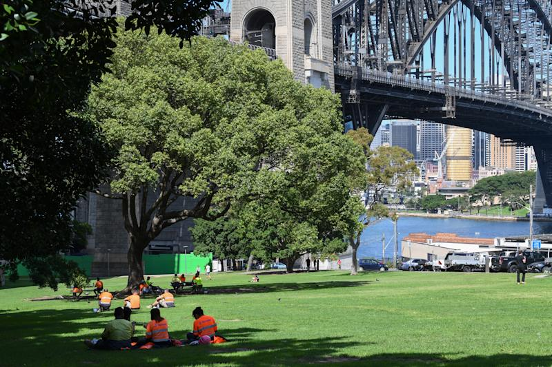 SYDNEY, AUSTRALIA - MARCH 31: Construction workers having their lunch break and enjoying the afternoon sunshine despite new restrictions on March 31, 2020 in Sydney, Australia. Public gatherings are now limited to two people, as the Australian Government introduces tougher restrictions in response to the COVID-19 pandemic. Prime Minister Scott Morrison on Sunday told Australians to stay home unless they are shopping for food, receiving medical attention, going to work or education, or for exercise, which is now limited to groups of two. People over 70 have been told to remain inside while public areas such as playgrounds, outside gyms and skateparks will be closed from midday on Monday. International arrivals into Australia are being quarantined in hotels on arrival. (Photo by James D. Morgan/Getty Images)