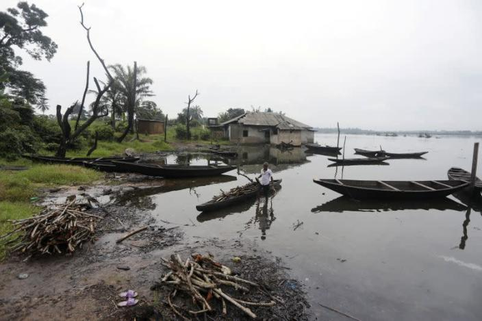 A man removes pieces of wood from a canoe in Ogoniland, Rivers State