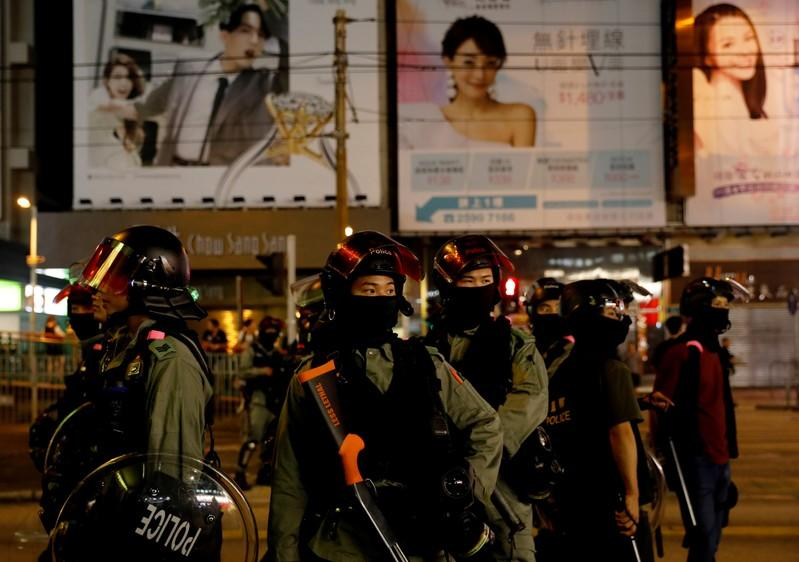 Riot police stand in position to disperse pro-democracy demonstrators gathering to commemorate the three-month anniversary of an assault by more than 100 men on protesters, commuters and journalists, in Hong Kong