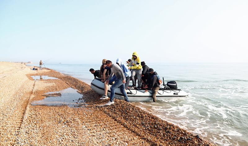 An angler watches as a group of people thought to be migrants arrive in an inflatable boat at Kingsdown beach, near Dover, Kent, after crossing the English Channel.