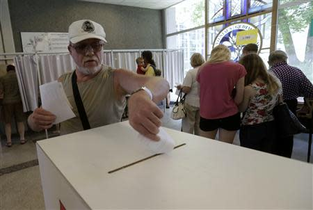 A man casts his vote during European Parliament and Lithuania's presidential elections in Vilnius May 25, 2014. REUTERS/Ints Kalnins