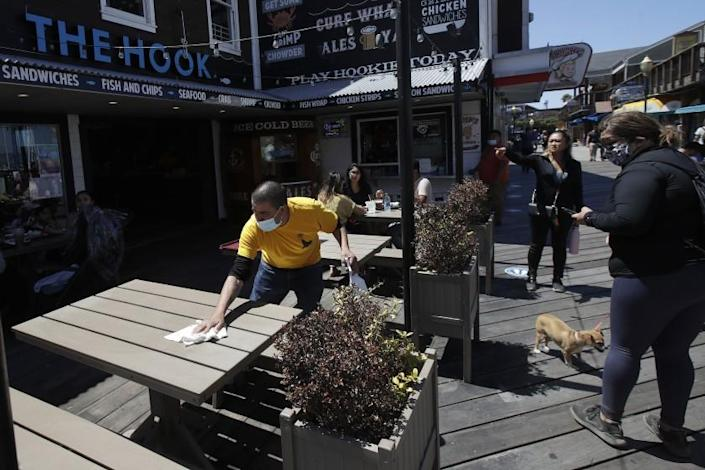 FILE - In this June 18, 2020, file photo, a man wears a face mask while cleaning an outdoor dining table at The Hook at Pier 39 in San Francisco. Restaurants and gyms are warning they cannot survive under California's new set of rules outlining when businesses can reopen during the coronavirus pandemic. Gov. Gavin Newsom announced a new, color-coded process Friday, Aug. 28, 2020, for reopening California businesses amid the coronavirus pandemic that is more gradual than the state's current rules to guard against loosening restrictions too soon.(AP Photo/Jeff Chiu, File)