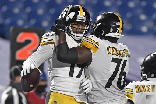 Pittsburgh Steelers wide receiver JuJu Smith-Schuster (19) celebrates with Chukwuma Okorafor after taking a 3-yard touchdown pass from quarterback Ben Roethlisberger during the second half of an NFL football game against the Buffalo Bills in Orchard Park, N.Y., Sunday, Dec. 13, 2020. (AP Photo/Adrian Kraus)