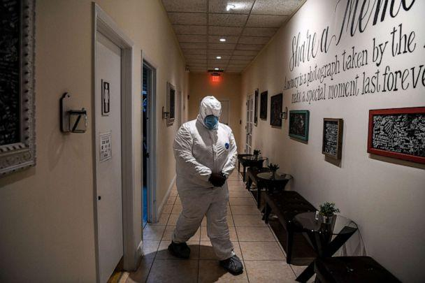 PHOTO: Funeral assistant, Bradley Georges, 26 wearing a PPE kit prior to a funeral at one of Miami's largest funeral homes, Van Orsdel funeral homes in Miami, on July 17, 2020. (Chandan Khanna/AFP via Getty Images)