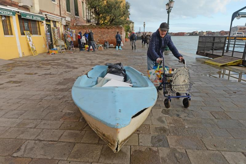 An elderly man passes by a boat left ashore following a flooding in Venice, Italy, Thursday, Nov. 14, 2019. The worst flooding in Venice in more than 50 years has prompted calls to better protect the historic city from rising sea levels as officials calculated hundreds of millions of euros in damage. The water reached 1.87 meters above sea level Tuesday, the second-highest level ever recorded in the city. (Andrea Merola/ANSA via AP)