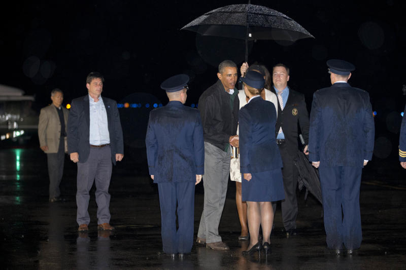 President Barack Obama, center, with first lady Michelle Obama partially obscured by a greeter, shakes hands as the first family boards Air Force One at Cape Cod Coast Guard Air Station, Mass., on Sunday August 18, 2013, at the conclusion of their family vacation on the island of Martha's Vineyard. (AP Photo/Jacquelyn Martin)