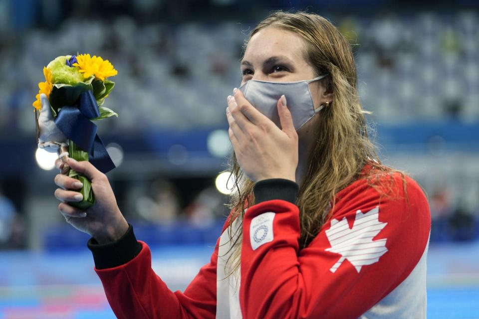 Woman holding a bouquet of flowers beams from behind a medical face mask.