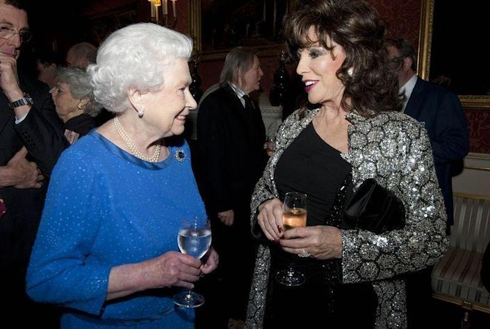 <p>Joan Collins isn't the muted outfit type—and the silver metallic jacket she wore to meet the Queen is proof. She *almost* upstaged the Queen, but everyone knows that's impossible, so, moving on!</p>