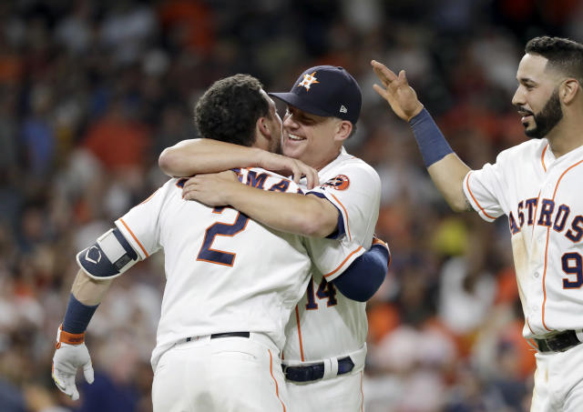 Houston Astros manager AJ Hinch (14) hugs Alex Bregman (2) after Bregman hit a game-winning double to score two runs against the Tampa Bay Rays during the ninth inning of a baseball game Monday, June 18, 2018, in Houston. The Astros won 5-4. (AP Photo/David J. Phillip)