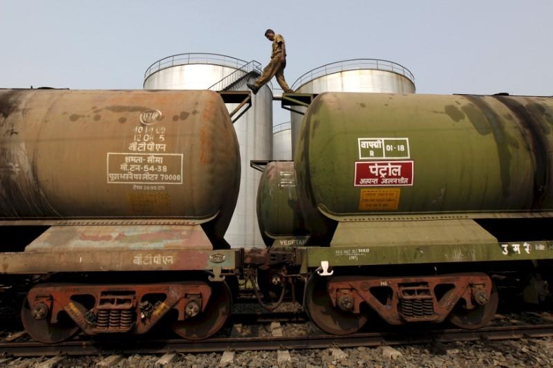 A worker walks atop a tanker wagon to check the freight level at an oil terminal on the outskirts of Kolkata, November 27, 2013. REUTERS/Rupak De Chowdhuri/Files