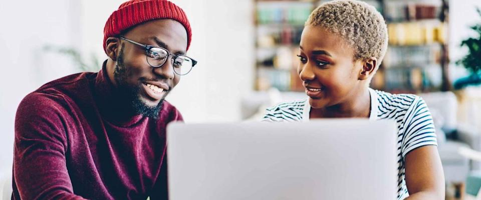 An African-American couple browses the website on a laptop, looking for low mortgage rates.