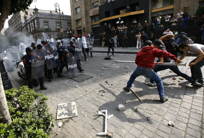 Protestors attempt to intimidate riot police with a pole in the streets of downtown Mexico City, Saturday, Dec. 1, 2012. Protests against Mexico's newly sworn-in President Enrique Pena Nieto began early Saturday morning with violent confrontations in the streets and protest speeches from opposition parties inside the congress. Protestors continued through the afternoon, vandalizing downtown businesses, smashing storefront glass windows and setting office furniture ablaze. (AP Photo/Marco Ugarte)