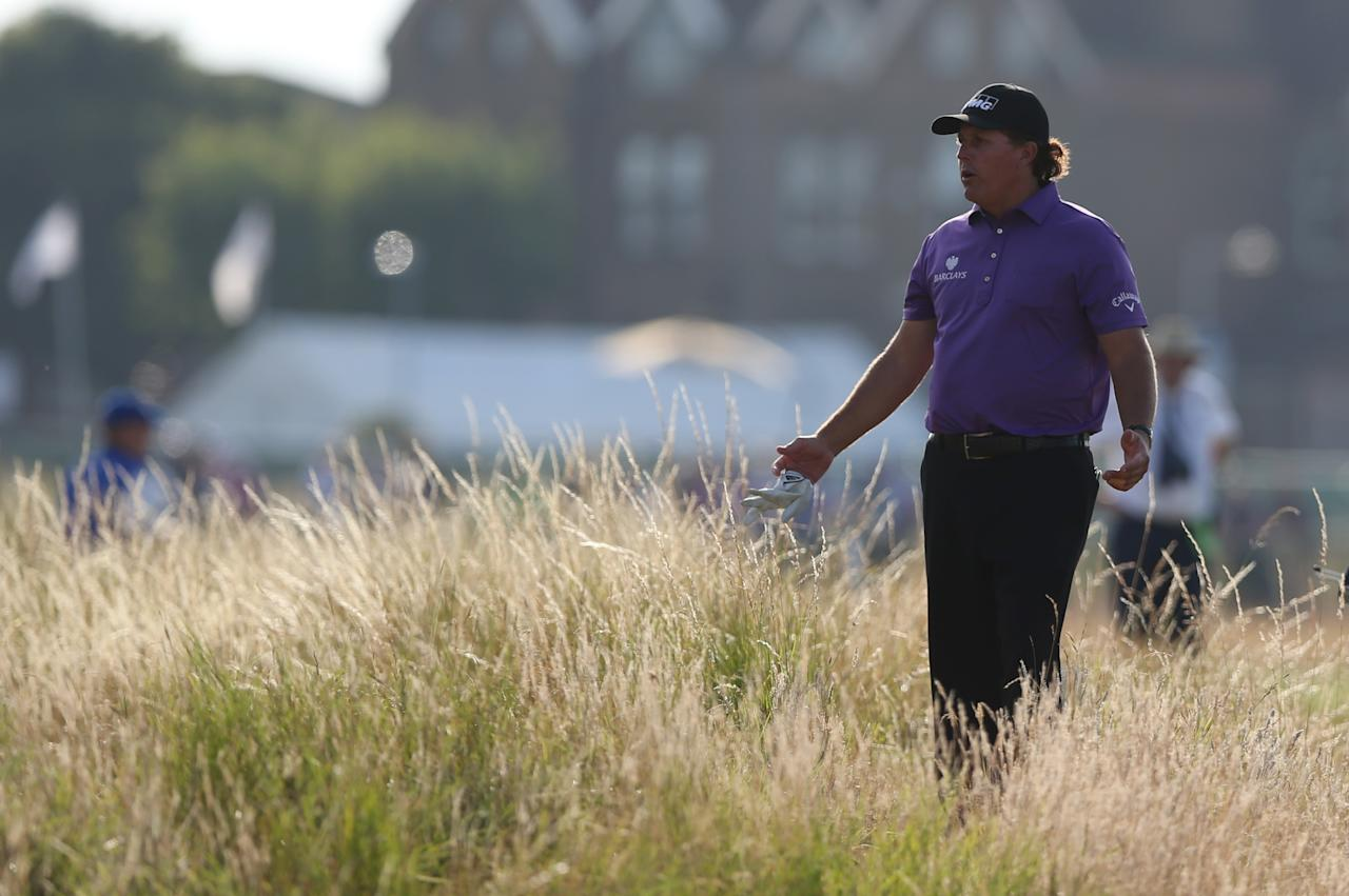 Phil Mickelson of the US looks for his ball in the rough on the 18th hole during the first day of the British Open Golf championship at the Royal Liverpool golf club, Hoylake, England, Thursday July 17, 2014. (AP Photo/Jon Super)