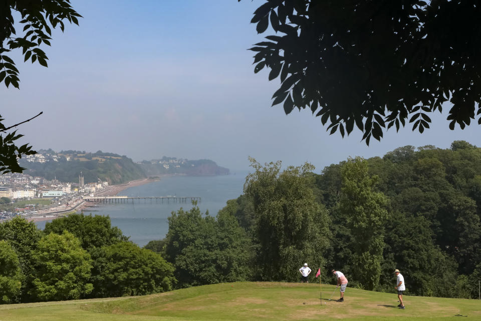People play on one of the greens of the pitch and put golf course in Shaldon, Devon, England, Thursday July 22, 2021. In the background is Teignmouth and the pier. (AP Photo/Tony Hicks)