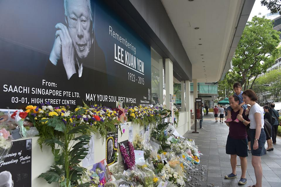 A family looks on in front of a memorial portrait of Singapore's late former prime minister Lee Kuan Yew outside the parliament building where he lies in state ahead of his funeral in Singapore on March 28, 2015. Singapore's first prime minister Lee Kuan Yew, one of the towering figures of post-colonial Asian politics, died at the age of 91 on March 23. AFP PHOTO / ADEK BERRY        (Photo credit should read ADEK BERRY/AFP via Getty Images)