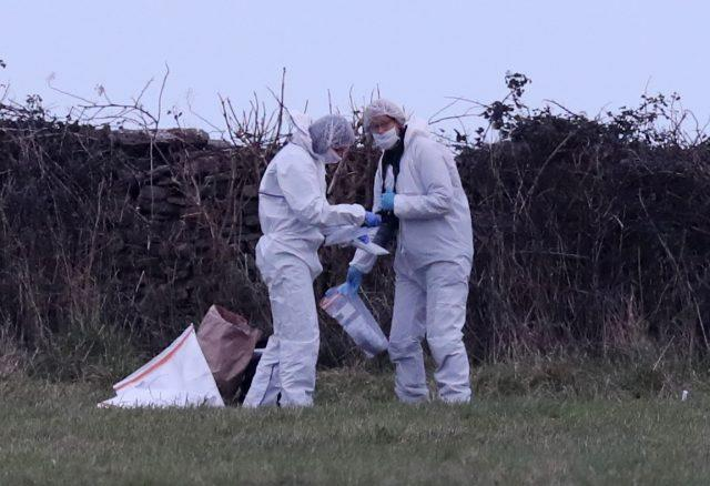 Forensic officers at work on a stretch of coastline near Swanage, close to where detectives have discovered items of women's clothing in a field