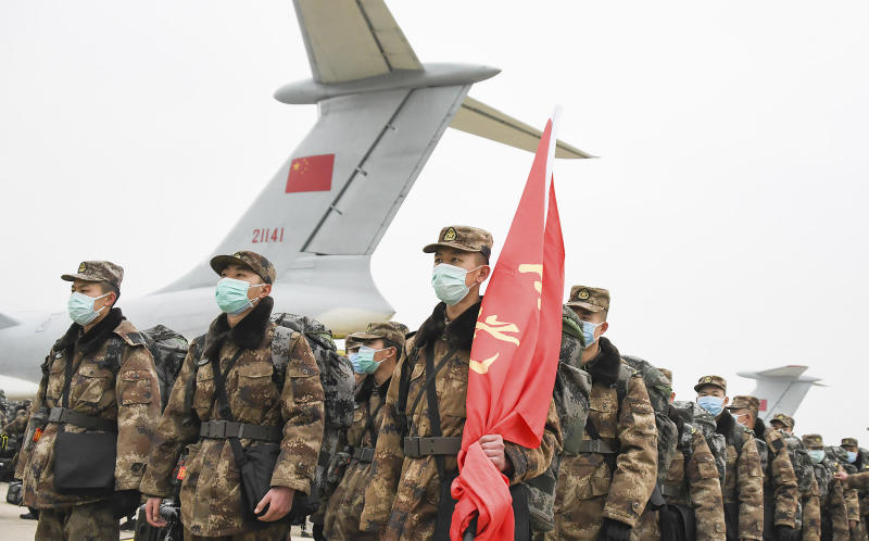 In this photo released by China's Xinhua News Agency, Chinese military medical staff members stand in formation after arriving at Wuhan Tianhe International Airport in Wuhan in central China's Hubei Province, Sunday, Feb. 2, 2020. The Philippines on Sunday reported the first death from a new virus outside of China, where authorities delayed the opening of schools in the worst-hit province and tightened quarantine measures in a city that allow only one family member to venture out to buy supplies. (Cheng Min/Xinhua via AP)