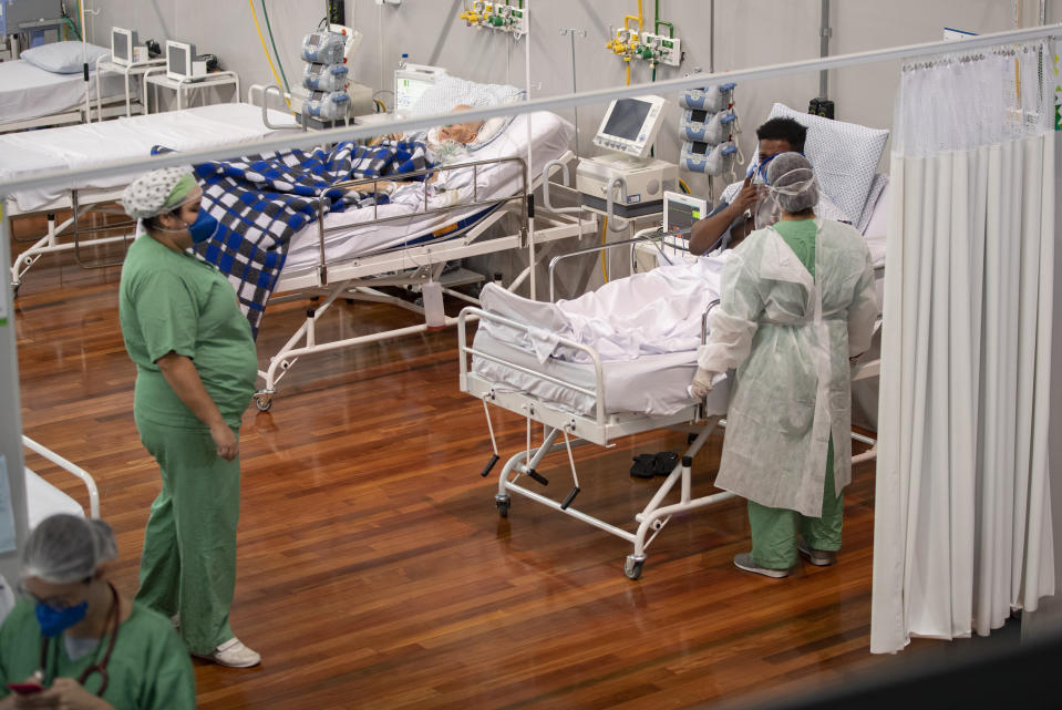 COVID-19 patients receive treatment as they lie on beds in a field hospital built inside a gym in Santo Andre, on the outskirts of Sao Paulo, Brazil, Tuesday, June 9, 2020. (AP Photo/Andre Penner)