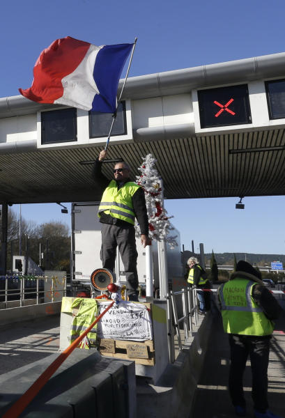 A demonstrators wearing a yellow vest waves a French flag as demonstrators open the toll gates on a motorway near Aix-en-Provence, southeastern France, Tuesday, Dec. 4, 2018. French Prime Minister Edouard Philippe announced a suspension of fuel tax hikes Tuesday, a major U-turn in an effort to appease a protest movement that has radicalized and plunged Paris into chaos last weekend. (AP Photo/Claude Paris)