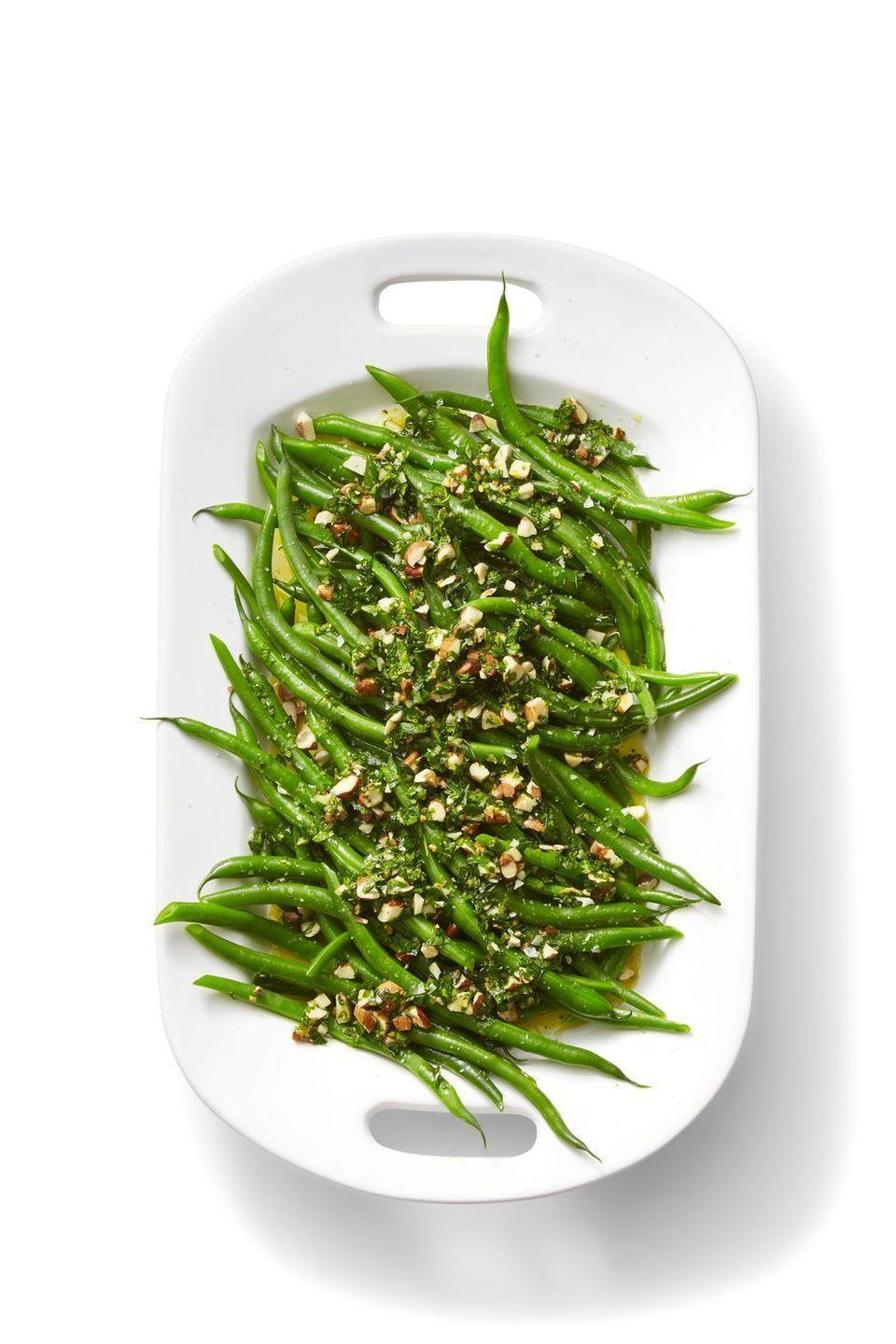 """<p>Flavor plain greens with rosemary, garlic, and orange zest for a fresh and easy side. </p><p><em><a href=""""https://www.womansday.com/food-recipes/food-drinks/a24115941/green-beans-with-orange-and-almond-gremolata-recipe/"""" rel=""""nofollow noopener"""" target=""""_blank"""" data-ylk=""""slk:Get the recipe from Woman's Day »"""" class=""""link rapid-noclick-resp"""">Get the recipe from Woman's Day »</a></em></p><p><strong>RELATED: </strong><a href=""""https://www.goodhousekeeping.com/holidays/thanksgiving-ideas/g803/green-beans/"""" rel=""""nofollow noopener"""" target=""""_blank"""" data-ylk=""""slk:31 Green Bean Recipes For Thanksgiving That Will Make These Veggies the Life of the Party"""" class=""""link rapid-noclick-resp"""">31 Green Bean Recipes For Thanksgiving That Will Make These Veggies the Life of the Party</a></p>"""