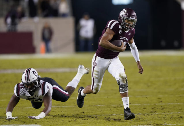 Texas A&M quarterback Kellen Mond, right, breaks away from South Carolina defensive lineman Kingsley Enagbare (52) as he rushes for a first down during the second quarter of an NCAA college football game Saturday, Nov. 16, 2019, in College Station, Texas. (AP Photo/David J. Phillip)