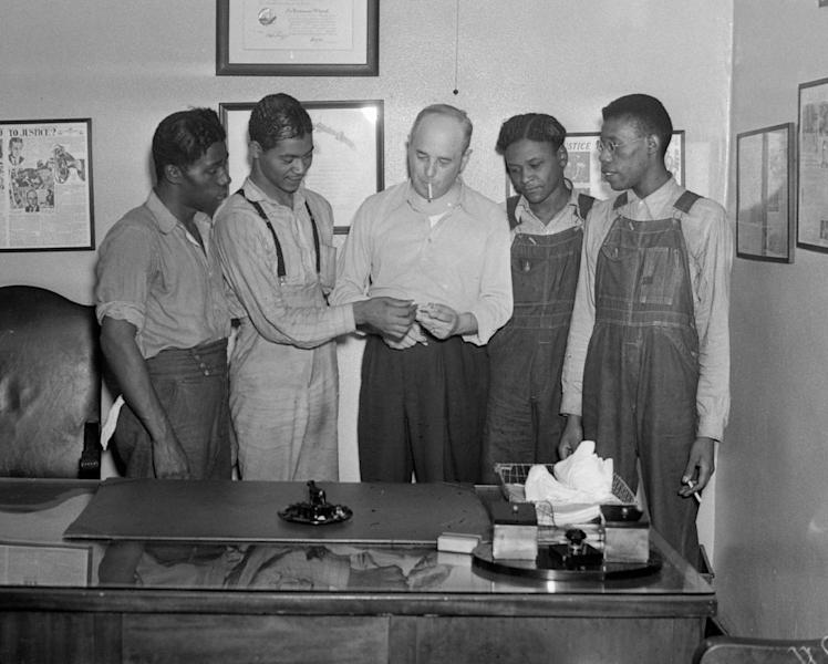 "FILE - In this July 26, 1937 file photo, New York attorney Samuel Leibowitz, center, stands in his office in New York with four of the ""Scottsboro Boys,"" from left, Willie Robertson, Eugene Williams, Roy Wright, and Olen Montgomery. Levin is credited with saving from death all but one of the nine black teens who were wrongly convicted of raping two white women in 1931. In a final chapter to one of the most important civil rights episodes in American history, Alabama lawmakers voted Thursday, April 4, 2013 to give posthumous pardons to the ""Scottsboro Boys"". (AP Photo, File)"