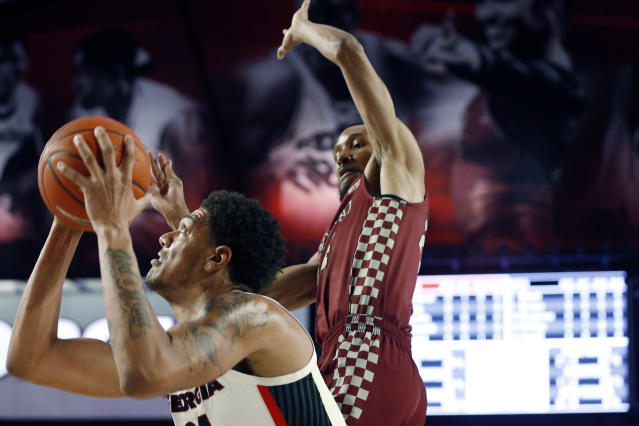 Georgia's Rodney Howard (24) looks to shoot while being defended by North Carolina Central's Nicolas Fennell (24) during an NCAA college basketball game Wednesday, Dec. 4, 2019, in Athens, Ga. (Joshua L. Jones/Athens Banner-Herald via AP)