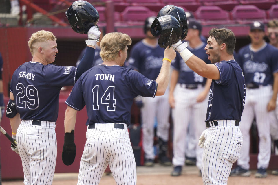 Dallas Baptist's Glenn Jackson, right, celebrates with Jace Grady (29) and River Town (14) after hitting a home run in the third inning during an NCAA college baseball tournament super regional game against Virginia on Monday, June 14, 2021, in Columbia, S.C. (AP Photo/Sean Rayford)