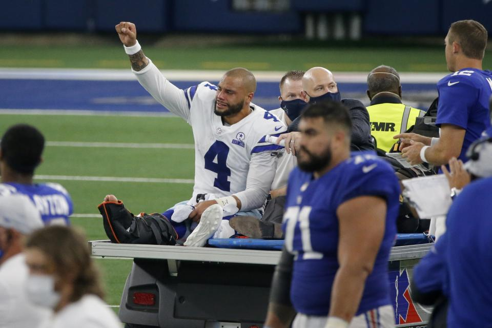 Dak Prescott lifts his fist on the back of a cart with an air cast on his right leg.