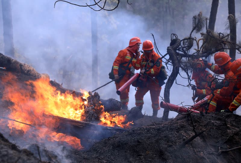 Firefighters work on extinguishing a forest fire that started near Xichang in Liangshan prefecture