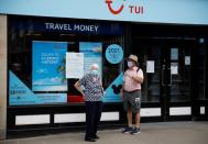 FILE PHOTO: People wear face coverings as they stand outside a Tui travel agents shop following the outbreak of the coronavirus disease (COVID-19) in Chester, Britain