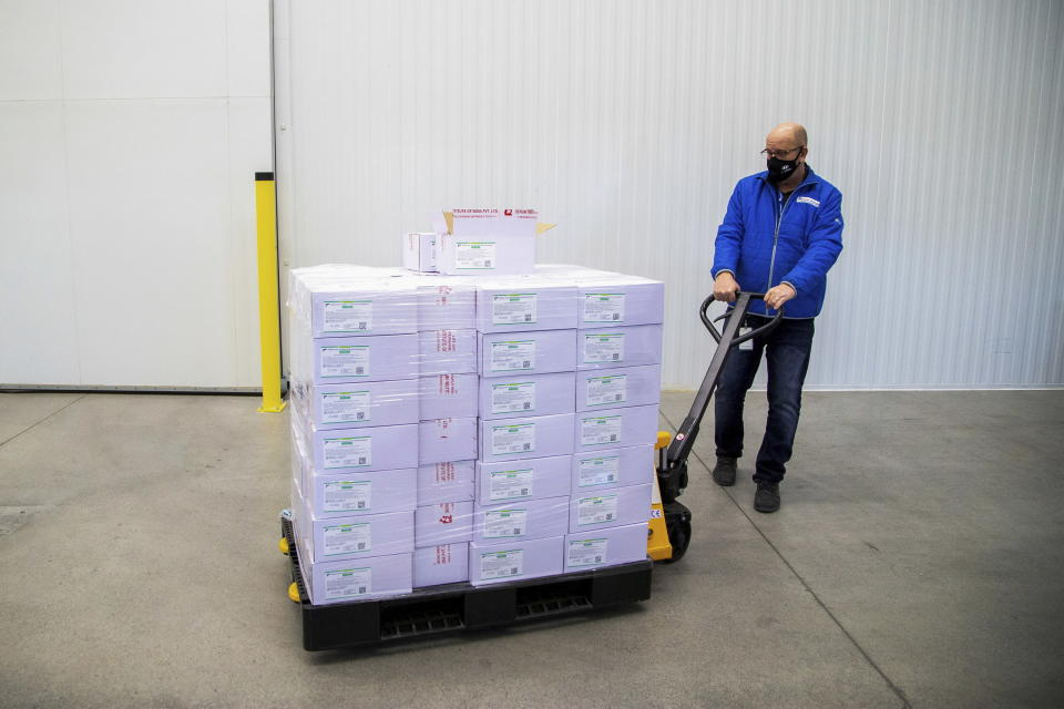 Michael Gray moves a pallet of some of the first 500,000 of the two million AstraZeneca COVID-19 vaccine doses that Canada has secured through a deal with the Serum Institute of India in partnership with Verity Pharma Wednesday, March 3, 2021, at a facility in Milton, Ontario. (Carlos Osorio/Pool Photo via AP)