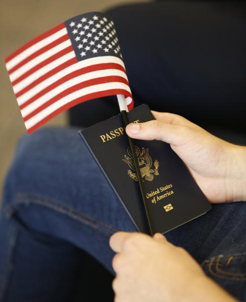 FILE - In this Aug. 30, 2018, file photo, a new citizens holds an American flag and passport during a naturalization ceremony at the U.S. Citizenship and Immigration Services Kendall Field Office in Miami. A growing number of Americans say immigration should remain the same or be increased since the Trump administration ramped up immigration enforcement. That's according to the General Social Survey, which has also found a growing partisan divide on the topic. The poll shows 34 percent of Americans want immigration to be reduced, down from 41 percent in 2016. It's the first time since the question was asked in 2004 that more Americans want immigration levels to stay the same than to be reduced. (AP Photo/Wilfredo Lee, File)