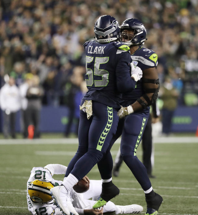 Seattle Seahawks defensive end Rasheem Green, right, celebrates with defensive end Frank Clark (55) after Green sacked Green Bay Packers quarterback Aaron Rodgers, lower left, during the second half of an NFL football game Thursday, Nov. 15, 2018, in Seattle. (AP Photo/Elaine Thompson)