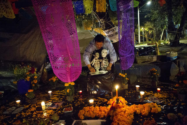 <p>A young man arranges skeletons on a Day of the Dead altar at a tent encampment at Multifamiliar Tlalpan, where nine people died when a building collapsed in the Sept. earthquake, in Mexico City, Tuesday, Oct. 31, 2017. People in Mexico are marking this year's holiday by remembering the people killed in the Sept. 19 earthquake. (Photo: Rebecca Blackwell/AP) </p>