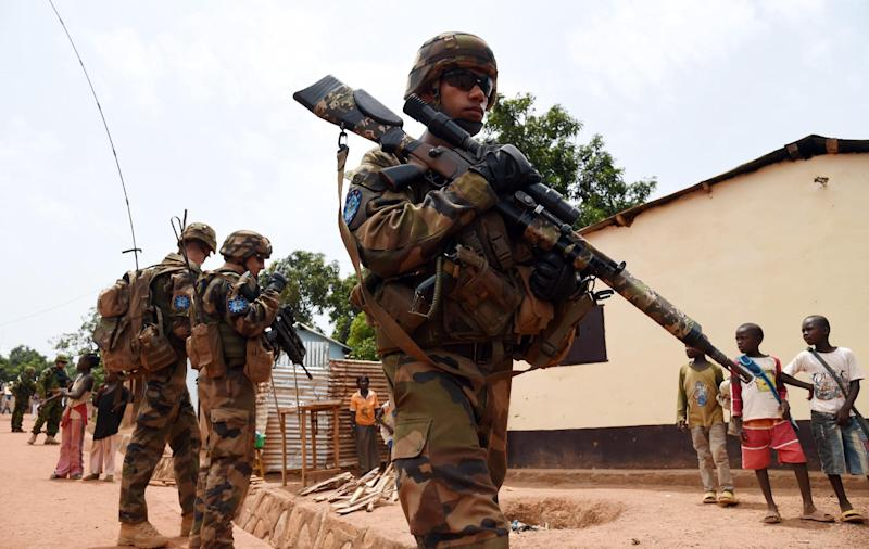French and Estonian soldiers of the European Union Force in the Central African Republic (EUFOR-CAR) patrol a street in Bangui on May 8, 2014