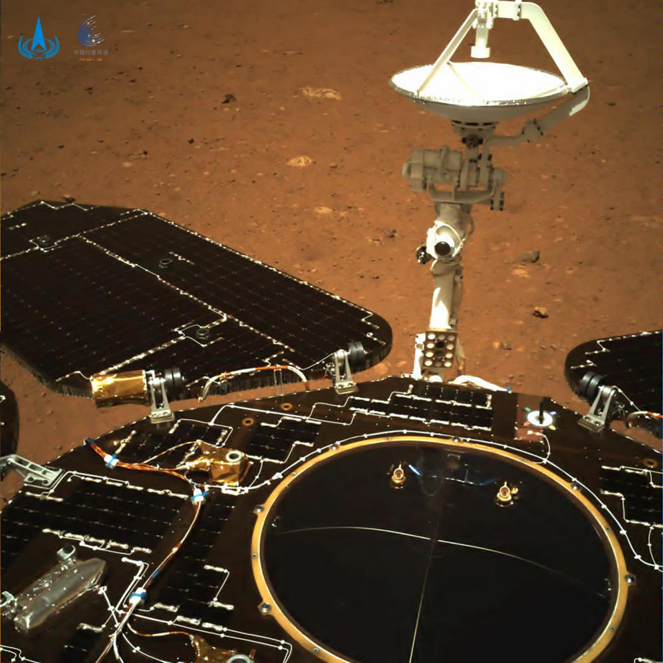 In this photo taken by China's Zhurong Mars rover and made available by the China National Space Administration (CNSA) on Wednesday, May 19, 2021, the rover's solar panels and antenna are deployed as the rover sits on its lander on the surface of Mars. China landed a spacecraft on Mars for the first time on Saturday, a technically challenging feat more difficult than a moon landing, in the latest step forward for its ambitious goals in space. (CNSA via AP)
