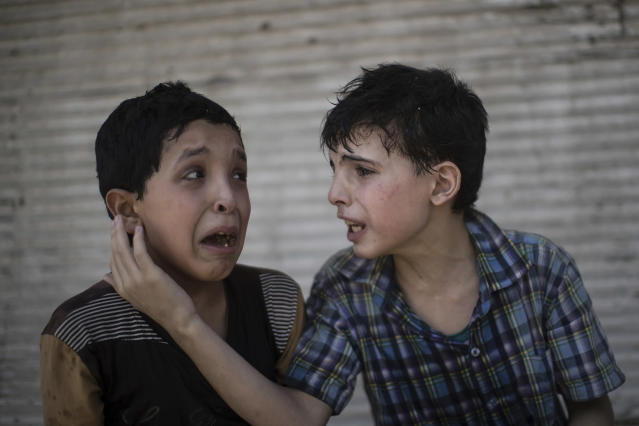<p>Zeid Ali, 12, left, and Hodayfa Ali, 11, comfort each other after their house was hit and collapsed during fighting between Iraqi forces and Islamic State militants in Mosul, Iraq, Saturday, June 24, 2017. The Ali cousins said some of their family members are still under the rubble. (Photo: Felipe Dana/AP) </p>