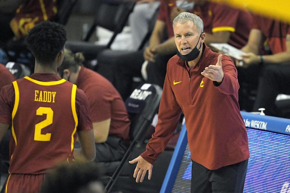 USC coach Andy Enfield, right, talks with guard Tahj Eaddy during the first half March 6, 2021.